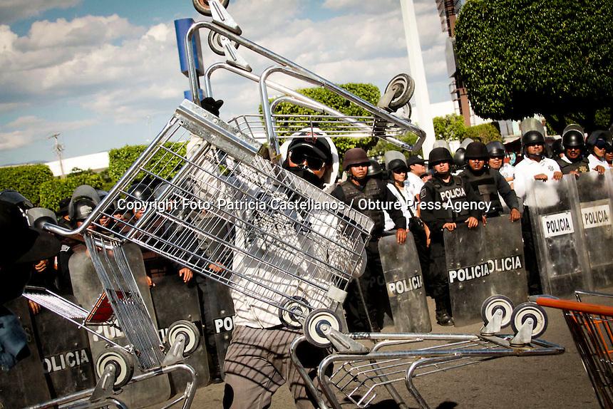 Oaxaca de Ju&aacute;rez. 20 de marzo de 2014.- Encapuchados, armados con palos, y bombas molotov,  integrantes de la Coordinadora Estudiantil de Normales del Estado de Oaxaca (CENEO), secuestraron 20 autobuses de transporte p&uacute;blico, para posteriormente llevarlos al centro comercial denominado &ldquo;Plaza Oaxaca&rdquo;, donde tomaron las instalaciones de los negocios que congrega este establecimiento por alrededor de 7 horas.<br /> <br />  <br /> <br /> Con una actitud agresiva hacia la prensa, los pseudo estudiantes, escud&aacute;ndose en la exigencia de sus demandas las cuales incluyen la adquisici&oacute;n autom&aacute;tica de plazas, tomaron este centro comercial, mismo en el que se encuentra ubicada la tienda departamental Soriana donde tuvieron retenidas a personas civiles y algunos trabajadores de este lugar.<br /> <br />  <br /> <br /> Los normalistas usaron los carritos de transporte de art&iacute;culos de dicha tienda para hacer una barricada y poder resguardarse de los elementos de seguridad p&uacute;blica de la polic&iacute;a estatal, quienes solo llegaron al lugar a observar los actos vand&aacute;licos de estos sin hacer nada.<br /> <br />  <br /> <br /> Los encapuchados permanecieron en la zona haciendo destrozos, y pintas en esta plaza comercial para luego de una mesa de dialogo con funcionarios estatales, los poco m&aacute;s de 300 manifestantes liberaron el lugar, no sin antes romper los cristales de un negocio que alberga dicho centro comercial, y huir en los camiones que hab&iacute;an secuestrado.<br /> <br />  <br /> <br /> Cabe destacar que a pesar de los actos vand&aacute;licos que hicieron este d&iacute;a, y vienen haciendo con sus movilizaciones estos pseudo estudiantes del CENEO, el gobierno del estado se mantiene ap&aacute;tico ante esta situaci&oacute;n, pero se muestra complaciente a las demandas parciales de los normalistas.<br /> <br /> <br /> <br /> Foto: Patricia Castellanos / Obture Press Agency.