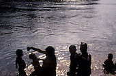 A-Ukre Village, Brazil. Kayapo Indian women and children washing in the Xingu river in the late afternoon.