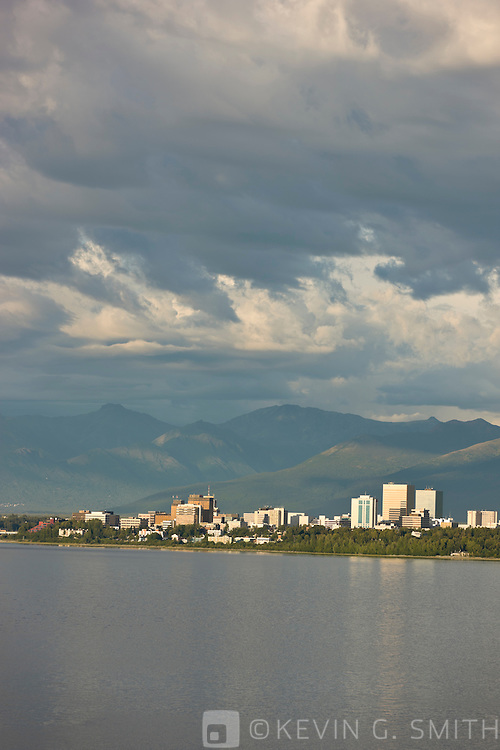 Thunderstorm clouds above the Anchorage, the city skyline reflected in the waters of Knik Arm at high tide, afternoon light, Chugach mountains in the background, Anchorage, Southcentral Alaska, Summer.