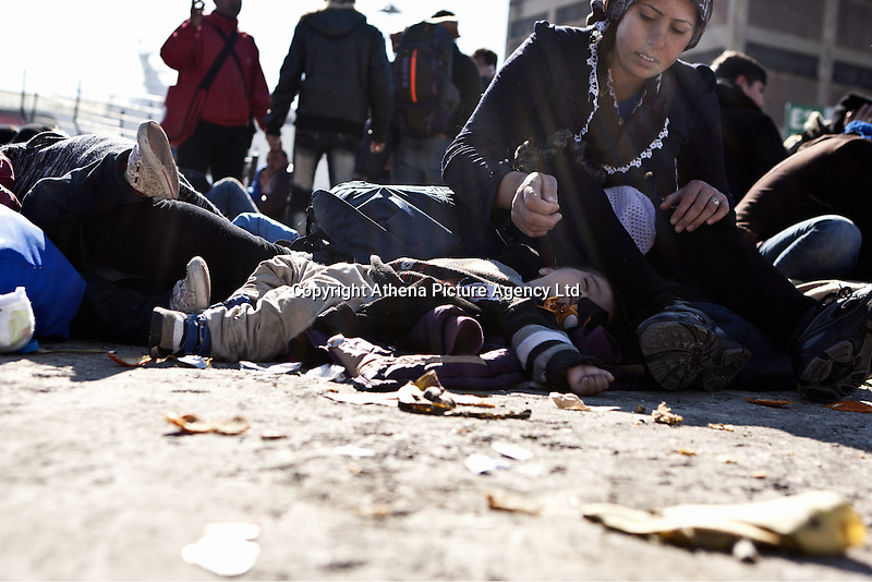 Pictured: A young child sleeps on the ground next to his mother Monday 22 February 2016<br /> Re: Thousands of migrants, most from Syria, have landed to the port of Pireaus, after crossing the border from Turkey to various islands like Lesvos and Kos in Greece.