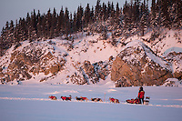 Paul Gebhart on the Bering Sea with the rocks of Elim in the background after leaving the Elim checkpoint on Tuesday March 12, 2013...Iditarod Sled Dog Race 2013..Photo by Jeff Schultz copyright 2013 DO NOT REPRODUCE WITHOUT PERMISSION