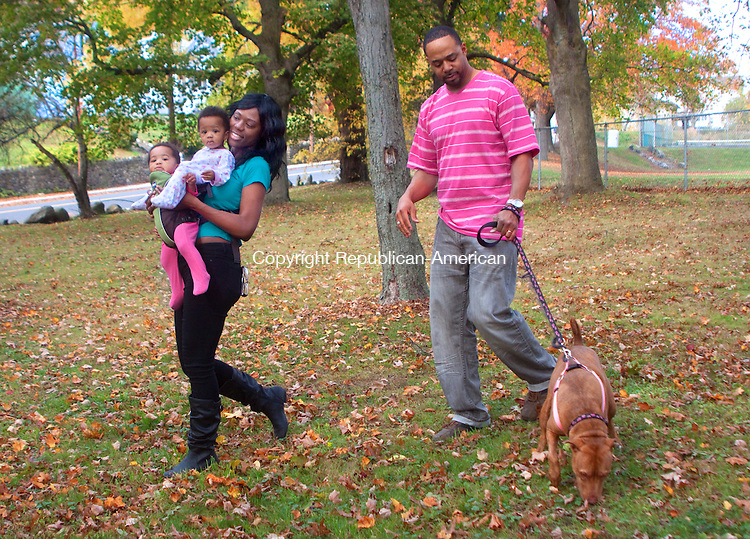 WATERBURY- OCTOBER 29 2014 102914DA01- Marlena Harris of Waterbury carries her 9 month old, twin girls Scarlett May, left, and Skye Lee along side of her husband Dana and their dog Precious. The family enjoyed the mild weather and beautiful foliage as they took a walk through Fulton Park in Waterbury on Wednesday.Darlene Douty Republican American
