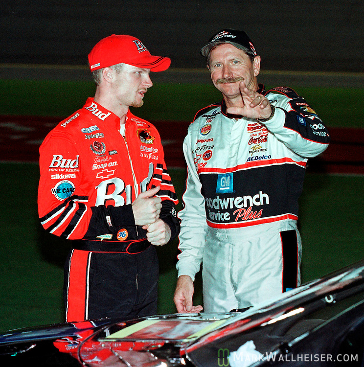 Dale Earnhardt (R) and Dale Earnhardt Jr. (L) talk on pit row just prior to the start of the Pepsi 400 this past season in 2000 at Daytona International Speedway...