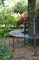 A wrought-iron circular seat encases a tree to provide a restful spot in the garden of Whitehouse, a B&B guest house in Chillington, Devon
