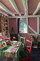 A cheerful table laid for tea in the living/dining area of the cottage where the table is spread with a checked tablecloth with a floral runner