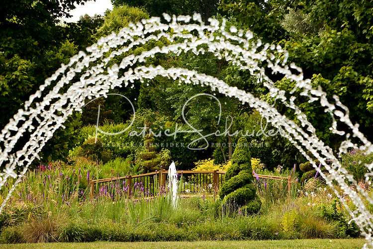 Streams of water arch overhead in the Tunnel Fountain Garden at Daniel Stowe Botanical Garden. The gardens attract plant, flower and gardening enthusiasts for its large manicured gardens, natural areas, woodland trails, water fountains and Orchid Conservatory. DSBG covers 380 acres of rolling meadows, woodlands and lakefront property in Belmont, NC. The gardens were founded by retired textile executive Daniel J. Stowe. Tended by employees and devoted volunteers, the garden has built a substantial reputation in and around the Carolinas. HGTV, Home and Garden Television, named Daniel Stowe Botanical Garden one of the nation's 20 Great Gardens.