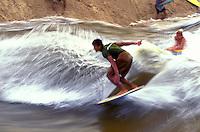 Two guys surfing the waves of Waimea Bay stream