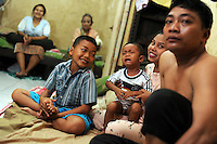 "30 year old Pak Sutrisno (right) sits in the ""home"" he and his family of six inhabit in the market complex of Porong town. A former resident of the now completely submerged Renokonongo village, Sutrisno was a rice farmer who has lost his land and his income in the mud flow disaster. Since May 2006, more than 10,000 people in the Porong subdistrict of Sidoarjo have been displaced by hot mud flowing from a natural gas well that was being drilled by the oil company Lapindo Brantas. The torrent of mud - up to 125,000 cubic metres per day - continued to flow three years later."