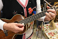 NWA Democrat-Gazette/FLIP PUTTHOFF <br /> SONGS FOR THE SEASON<br /> Mary Bourn sports a Christmas sweater while playing 8-string ukelele on Tuesday Dec. 4 2018 with the Old Town String Band at the Billy V. Hall Senior Activity and Wellness Center in Gravette. The band features musicians on guitar, mandolin, fiddle, ukelele, bass and more. They play at the Gravette senior center at 10 a.m. the first, second and third Tuesday of each month