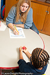 Education preschool 3-4 year olds female teacher administering development assesment psychological test to preschool student