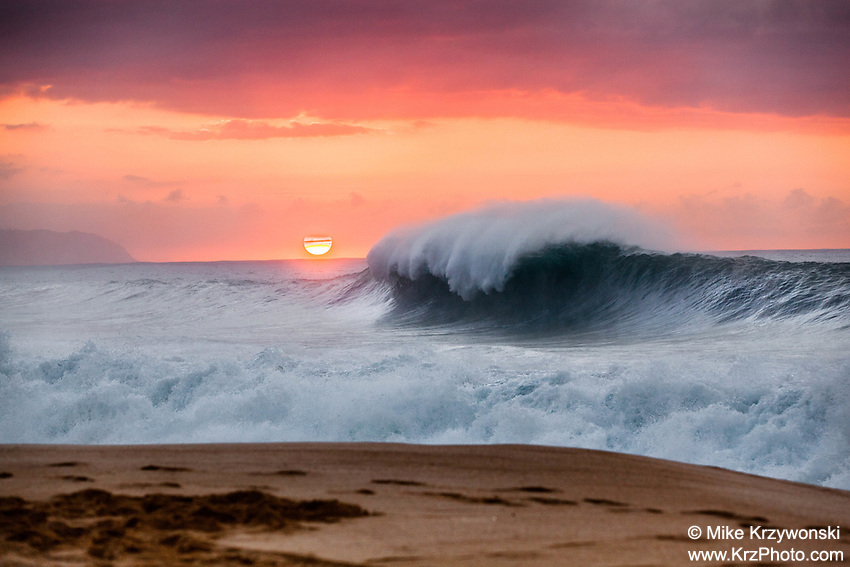 Wave breaking under orange sunset at Keiki Beach, North Shore, Oahu, Hawaii