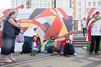 SARANSK, RUSSIA - June 25, 2018: A  resident of Saransk offers treats to Iran fans resting in Millennium Square in Saransk before the 2018 FIFA World Cup group stage match between Iran and Portugal at Mordovia Arena.