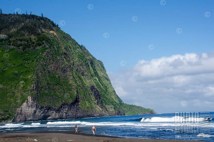 Two women walk along the black sand beach at Waipi'o Valley, Hamakua District, Island of Hawai'i.