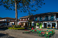 Colombian peasants sit in a coffee shop in front of the colonial houses at the main plaza of Jardín, a village in the coffee region (Zona cafetera) of Colombia, 1 December 2016.