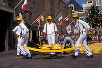 AJ2177, cheese market, Alkmaar, Netherlands, Europe, Costumed porters carrying wheels of cheese (Gouda and red-skinned Edam) on a sledge at the weekly Cheese Market on the Waagplein in Alkmaar.