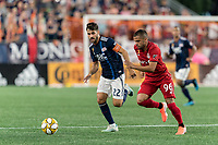 FOXBOROUGH, MA - AUGUST 31: Carles Gil #22 of New England Revolution and Auro Jr #96 of Toronto FC battle for the ball during a game between Toronto FC and New England Revolution at Gillette Stadium on August 31, 2019 in Foxborough, Massachusetts.