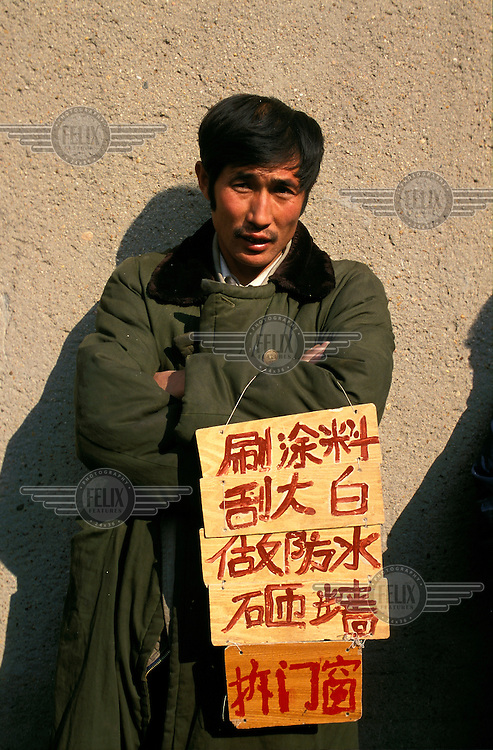 ©Mark Henley/Panos Pictures..China, Liaoning (Manchuria), Shenyang..Economic crisis. Unemployed. Laid-off state worker advertising his skills waiting for job offer on street.