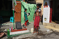 Local Kolkatans at a public water pump in central Kolkata, India. November, 2013