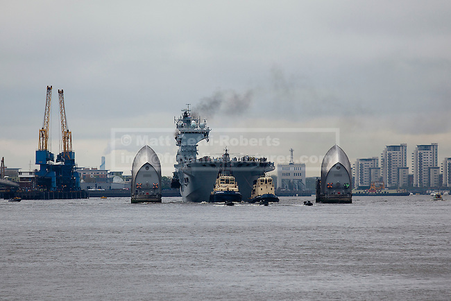 04/05/2012. LONDON, UK. The Royal Navy's helicopter carrier, HMS Ocean makes her way through the the Thames Barrier in London today (04/05/12). HMS Ocean has been deployed as part of an exercise involving the RAF, British Army and Royal Navy taking place across London as part of security preparations for the 2012 London Olympic Games. Photo credit: Matt Cetti-Roberts