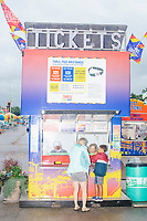People buy tickets on the midway at the start of a rainy day at the Iowa State Fair in Des, Moines, Iowa, on Sun., Aug. 11, 2019.