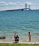 Mackinac Bridge from Bridge View Park in St. Ignace, Michigan. Family on beach.