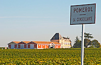 Pomerol vineyards - A sign with La Conseillante, with the chateau Evangile with winery in the background