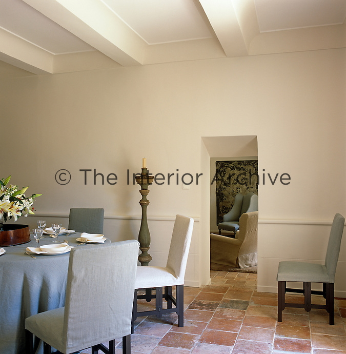 The dining room is simply furnished with a round table and chairs covered in grey linen and the floor is tiled with 18th century tiles