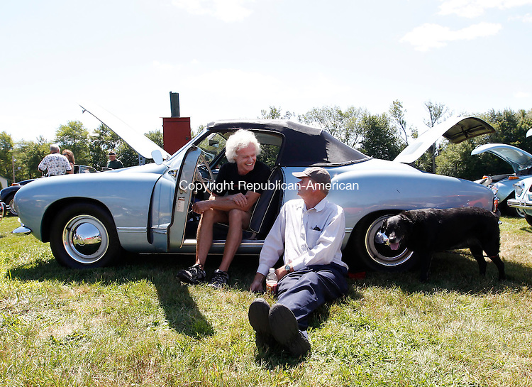 Terryville, CT- 11 August 2013-081113CM02-  Tim Friend, left, of Newport, RI sits in his 1958 Volkswagen Karmann Ghia as he jokes with Chuck Ackerman of Litchfield, during the 22nd annual Connecticut Bug-A-Fair Sunday morning at the Terryville Fair Grounds.  With them is Lucy, Friend's 8 year old Lab.  Ackerman brought his 1972 Karmann Ghia to the fair, where proceeds from the event, which is put on by the Terryville Lions Club, will go towards their many local charitable activities.        Christopher Massa Republican-American