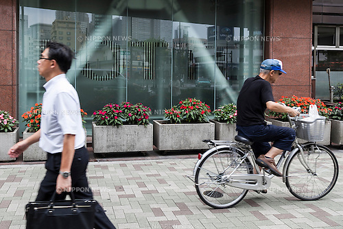 Pedestrians walk past the LOTTE Japan headquarters in Shinjuku on July 29, 2015, Tokyo, Japan. Shares in Lotte group companies jumped up on Wednesday as investors expect founding family members to try to increase their holdings. On Tuesday the board of Lotte Holdings had sacked 92-year-old founder Shin Kyuk-ho from his position as co-CEO. This led to speculation that other family members would try to compete for control of the Korean conglomerate. (Photo by Rodrigo Reyes Marin/AFLO)