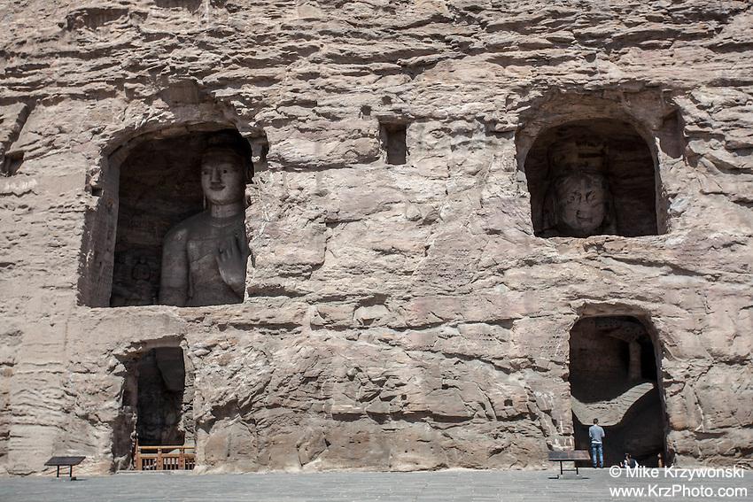 Visitors admiring large Buddha statues at the Yungan Grottoes in Datong, China