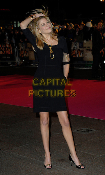"KRISTEN JOHNSTON.Attends the UK Premiere of ""Music & Lyrics"",.Odeon Leicester Square, .London, England, February 5th 2006..full length black dress hand touching hair gold necklace.CAP/CAN.©Can Nguyen/Capital Pictures"