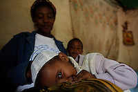 Magdass Albechew, daughter of HIV positive Emembet lies in the arms of her  her temporary host, senior home base care giver Asnagetch, while her mother is hospitalized in Addis Ababa, Ethiopia on Sunday July 09 2006. Emembet lives with her daughter, 3 years old Magdass, her only reason to live. On June 20th she was reported to be dead by the St Paul hospital staff while she was enduring a deep physical crises. after almost 4 weeks of hospitalization she was discharged and could finally reunite with her daughter that meanwhile lived with a local home base care giver. . Ethiopia is one of the countries most affected by HIV/AIDS. Of its population of 77 million, three million are HIV-positive, according to government statistics. Every day sees 1,000 new infections. A million children under 14 have lost one or both parents to AIDS, and 200,000 children are living with AIDS. That makes Ethiopia the country with the most HIV-positive children.