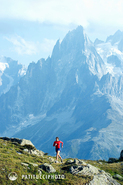 Lone trail runner running above Chamonix Valley in the French Alps with the Aiguilles in the background