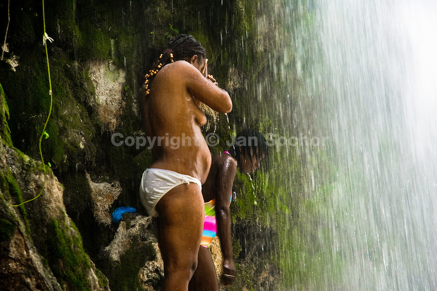 Haitian women perform a bathing and cleaning ritual under the waterfall during the annual religious pilgrimage in Saut d'Eau, Haiti, July 16, 2008. Every year in summer thousands of pilgrims from all over Haiti make the religious journey to the Saut d'Eau waterfall (100km north of Port-au-Prince). It is believed that 150 years ago the spirit of Virgin Mary (Our Lady of Mount Carmel) has appeared on a palm tree close to the waterfall. This place became a main pilgrimage site in Haiti since then. Haitians wearing only underwear perform a bathing and cleaning ritual under the 100-foot-high waterfall. Voodoo followers (many Haitians practise both voodoo and catholicism) hope that Erzulie Dantor, the Voodoo spirit of water, manifest itself and they get possessed for a short moment, touched by her presence.