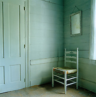 In the bedroom of this farmhouse in Upstate New York an antique ladder-back chair has been placed in a corner with an old mirror hanging on the clapboard wall behind