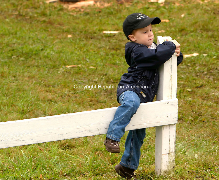 GOSHEN, CT-02 AUGUST 2006-090306JS05-During a break in the lumberjack competition at the Goshen Fair on Sunday, three-year-old Zackary Raymond of Hudson, Florida climbs back and fourth across a small wood fence. Zackary was visiting relatives in Goshen with his parents, who both grew up in there.    -Jim Shannon Republican-American