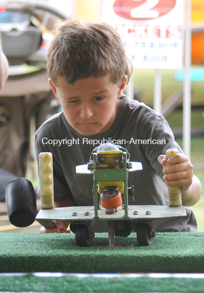 THOMASTON, CT-22 JULY 2010-072210IP07- Mac Stancavage, 8, of Thomaston carefully lines up his shot as he prepares to catapult a rubber frog with the swing of his mallot at the Frog Bog game during the Thomaston Fire Department's annual carnival at  Sanford Avenue Field in Thomaston on Thursday. The carnival features games, food and rides for all ages and will run through Saturday.<br /> Irena Pastorello Republican-American