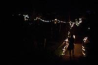 """A Wild Goose Festival-goer crosses a foot bridge near the """"Peace Garden"""" at the Shakori Hills Community Arts Center on June 22, 2012, the second night of the four-day festival in Pittsboro, NC."""