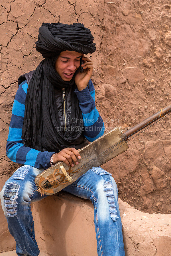 Morocco.  Teenage Amazigh Berber Musician with a Gimbrie, Talking on his cell Phone.  Ait Benhaddou Ksar, a World Heritage Site.