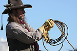 A cowboy on horseback bringing in his rope for catching cattle