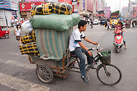 Daytime landscape view of a man driving a utility tricycle loaded with large packages on the street near the Qiao Jia Men in the Èrqī Qū of Zhengzhou in Henan province.  © LAN