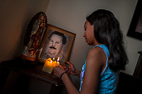 "A Colombian girl lights up the candles at the altar in honor of the drug lord Pablo Escobar, placed in the living room corner of a house in the Pablo Escobar neighborhood, Medellín, Colombia, 30 November 2017. Twenty five years after Pablo Escobar's death, the legacy of the Medellín Cartel leader is alive and flourishing. Although many Colombians who lived through the decades of drug wars, assassinations, kidnappings, reject Pablo Escobar's cult and his celebrity status, there is a significant number of Colombians who admire him, worshipping the questionable ""Robin Hood"" image he had. Moreover, in the recent years, the popular ""Narcos"" TV series has inspired thousands of tourists to visit Medellín, creating a booming business for many but causing a controversial rise of narco-tourism."