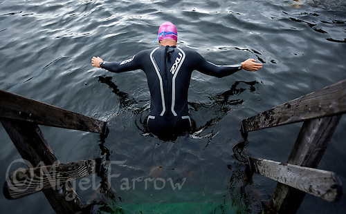 14 AUG 2010 - KITZBUEHEL, AUT - A competitor dives into the water as he warms up before his wave of the Jedermann Triathlon .(PHOTO (C) NIGEL FARROW)