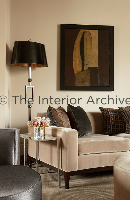An absract painting in hues of brown compliments the colour palette of this neural sophisticated living room