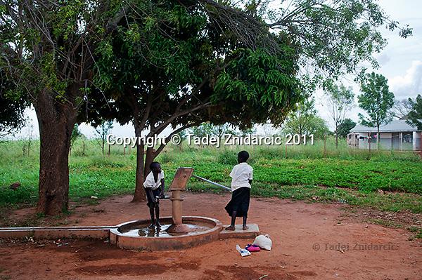 Children fetch water from a well at Orom Health Center III, Orom Village, Kitgum district.