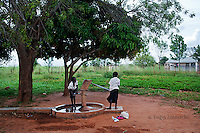 Children fetch water from a well at Orom Health Center III, Orom Village, Kitgum district.