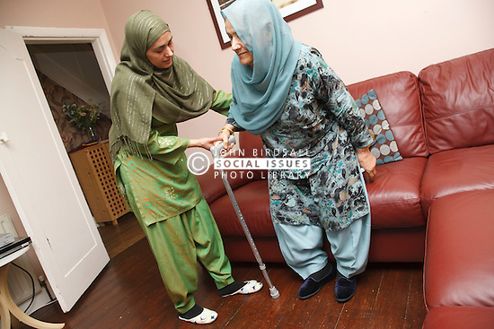 South Asian woman helping mother in law get up from sofa.