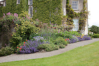 A well-stocked flowerbed in the lee of Burtown House overflows onto the gravel pathway in the garden
