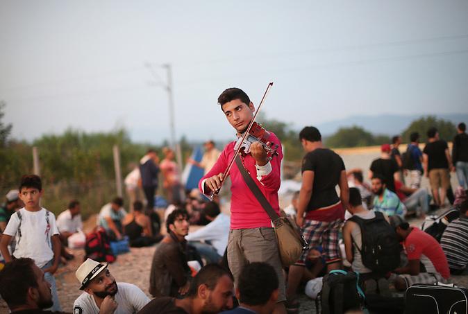 Sirec Rami Basisah spielt Geige, w&auml;hrend Hunderte von Fl&uuml;chtlingen  auf einen Zug nach Serbien warten Gevgelija, Mazedonien 27.August 2015.<br />/  Fl&uuml;chtlinge an der Grenze von Griechenland zu Mazedonien. Sie kommen von Griechenland und wollen &uuml;ber Serbien in die EU. // Refugees at the Greek-Macedonia border on August 31. 2015. On a daily basis thousands of refugees pass the border to get a train, bus or taxi to Serbia