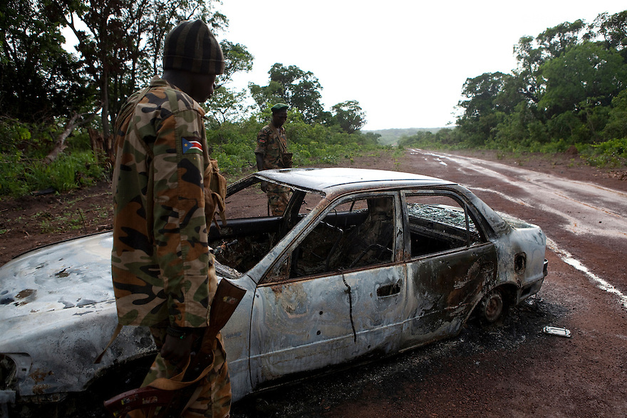 22 may 2010 - Western Equatoria State, South Sudan - Two SPLA soldiers inspect a car that was ambushed and burnt by the Lord's Resistance Army (LRA) on the road between Yambio and Tambura. The three victims were government officials in the State Ministry of Education: Mr. William Arkangelo Baabe, Mr. Gabriel Makana (49 years old) and Baraka Josefati (25 years old). The LRA has attacked a number of roads, villages, and clinics in the area over the last week pushing thousands of people to flee to larger towns for protection. Western Equatoria state has been rocked by LRA activities since 2006. Thousands of people have been forced from their homes as brutal attacks continue against the civilian population in the region and neighboring DRC and CAR. Photo credit: Benedicte Desrus